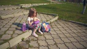 Ni?a rubia que come su almuerzo en parque el d?a soleado almacen de metraje de vídeo