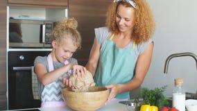 Ni?a y su madre que asperjan la harina en un cuenco y una hornada sonriente del rato metrajes