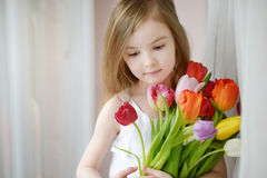 Niña adorable con los tulipanes por la ventana Foto de archivo