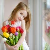 Niña adorable con los tulipanes por la ventana Imagenes de archivo