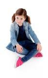 Niña adorable que se sienta en el piso con la camisa del dril de algodón Imagenes de archivo