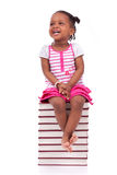 Niña afroamericana negra linda asentada en una pila de abucheo Fotos de archivo