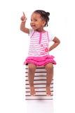 Niña afroamericana negra linda asentada en una pila de abucheo Imagenes de archivo