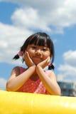 Niña asiática en el cielo azul Foto de archivo