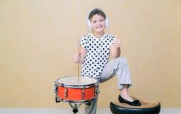 niña bonita alegre que coloca y que sostiene los palillos detrás de un tambor Imagenes de archivo