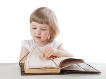 Niña bonita que lee un libro interesante Imagenes de archivo