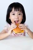 Niña china asiática feliz que come la hamburguesa Imagenes de archivo