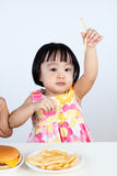 Niña china asiática que come las patatas fritas Foto de archivo