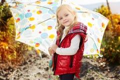 Niña con el paraguas en el chaleco rojo al aire libre Fotos de archivo