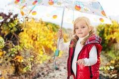 Niña con el paraguas en el chaleco rojo al aire libre Foto de archivo libre de regalías