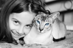 Niña con su gato siamés Imagenes de archivo