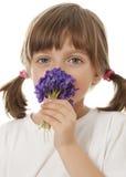 Niña con un ramo de violetas Imagenes de archivo
