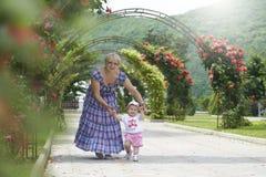 Niña de enseñanza de la abuela a caminar Fotografía de archivo libre de regalías