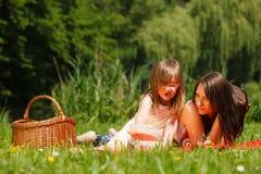 Niña de la madre y de la hija que tiene comida campestre en parque Fotografía de archivo libre de regalías
