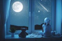 Niña del niño en la ventana que sueña y que admira el cielo estrellado en Fotos de archivo