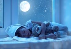 Niña del niño que duerme en la ventana que sueña y que admira el s Fotos de archivo libres de regalías