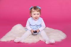 Niña divertida que juega con el teléfono móvil sobre fondo rosado Fotos de archivo