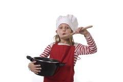 Niña en cocinar el sombrero y el delantal rojo que juegan el pote que se sostiene feliz sonriente del cocinero y que fingen la co Imagen de archivo libre de regalías