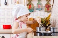 Niña en delantal en la cocina Imagen de archivo
