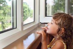 Niña en el balcón, mirada de la ventana Foto de archivo libre de regalías