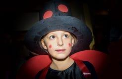 Niña en el traje de la mariquita para el maskenball de la escuela Fotos de archivo