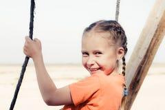 Niña en la playa en un oscilación Fotos de archivo libres de regalías