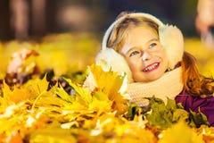 Niña en los earflaps que juegan con las hojas de otoño Imagen de archivo libre de regalías
