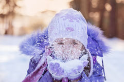 niña en sombrero caliente y guantes que soplan nieve Imágenes de archivo libres de regalías