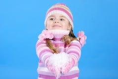 Niña en un suéter y un sombrero con la nieve Imagenes de archivo