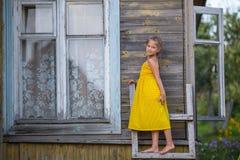 Niña en un vestido amarillo que se coloca en una escalera de madera cerca del cortijo Verano Imagen de archivo libre de regalías