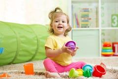 Niña feliz del niño que juega con los juguetes dentro Fotos de archivo