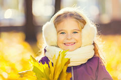 Niña feliz en earflaps con las hojas de otoño Fotografía de archivo