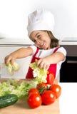 Niña feliz que juega con la cocina de las verduras en casa en sombrero del delantal y del cocinero Imagenes de archivo