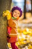 Niña feliz que juega en el parque del otoño Fotografía de archivo libre de regalías