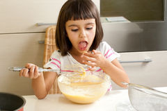 Niña feliz que prueba la mezcla para cocinar una torta Imagen de archivo