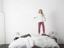 Niña feliz que salta en cama Imagen de archivo