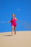 Niña feliz que se ejecuta abajo de las dunas de arena Imagenes de archivo