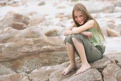 Niña feliz que se sienta en roca Imagenes de archivo