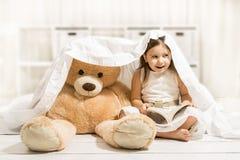 Niña hermosa que lee a su juguete del oso de peluche Imagenes de archivo