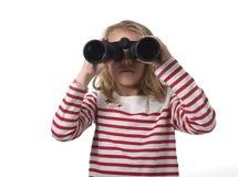 Niña joven del pelo rubio que mira que celebra la mirada de los prismáticos Foto de archivo libre de regalías