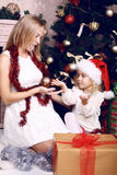Niña linda en el sombrero de Papá Noel que juega con su madre al lado de un árbol de navidad Imagenes de archivo