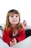 Niña linda en una mentira roja Fotos de archivo libres de regalías