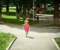 Niña linda feliz que corre en el parque felicidad Imagenes de archivo