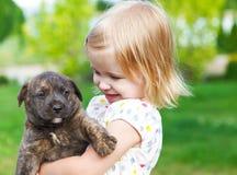 Niña linda que abraza el perrito del perro Imagen de archivo