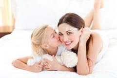 Niña linda que besa a su madre Imágenes de archivo libres de regalías