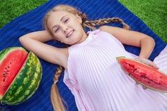 Niña linda que come la sandía en la hierba en tiempo de verano con el pelo largo de la cola de caballo y la sonrisa dentuda sentá Fotografía de archivo