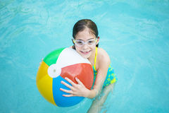 Niña linda que juega con la pelota de playa en una piscina Imagen de archivo libre de regalías