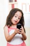 Niña linda que usa el teléfono celular Fotos de archivo libres de regalías