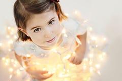 Niña linda, sonriente con las luces de la Navidad que brillan intensamente Fotografía de archivo