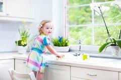 Niña pequeña hermosa en platos que se lavan del vestido colorido Imagen de archivo libre de regalías